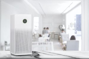 Air purifier in white workplace room with filter for cleaner removing fine dust.